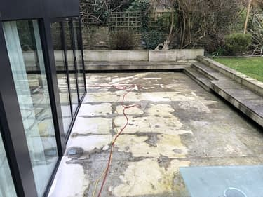 dirty Portland stone patio before patio cleaning service. Cobham Surrey